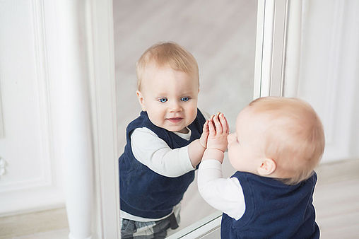 Ten month boy stands before the mirror